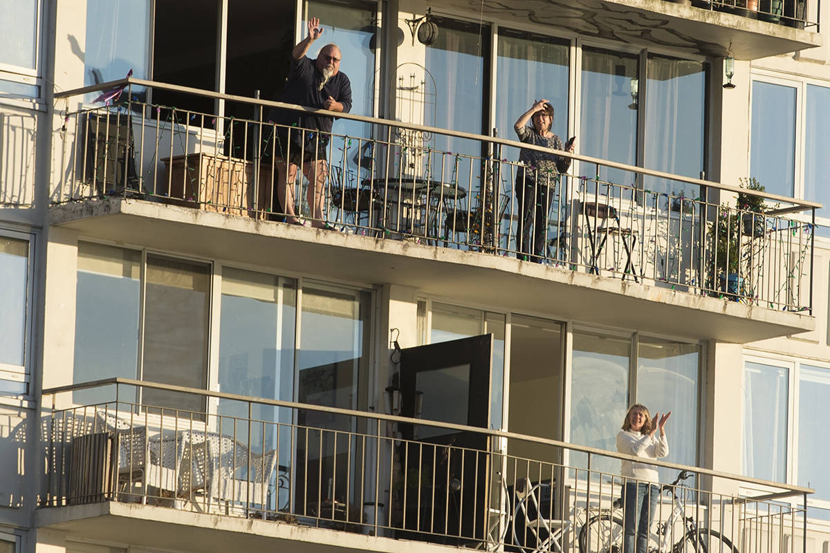 People are seen clapping on their balconies in Vancouver, B.C. Tuesday, March 24, 2020. Thousands of people in Vancouver's west end have been going out on their balconies to applaud the front line heath care workers each night at 7pm. THE CANADIAN PRESS/Jonathan Hayward