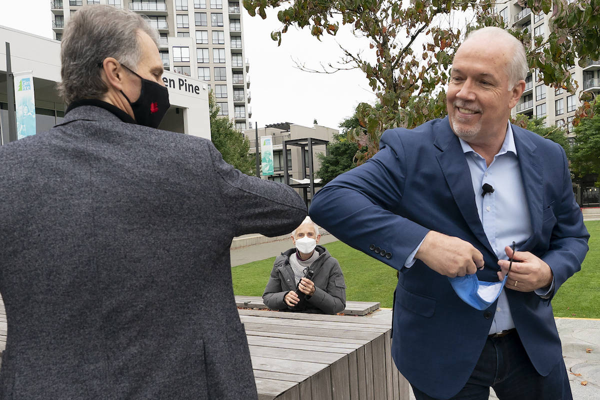 NDP Leader John Horgan elbow bumps NDP candidate Coquitlam-Burke Mountain candidate Fin Donnelly following a seniors round table in Coquitlam, B.C., Tuesday, October 20, 2020. THE CANADIAN PRESS/Jonathan Hayward